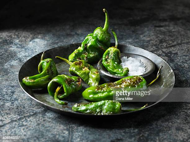 Green padron peppers in metal dish with bowl of sea salt