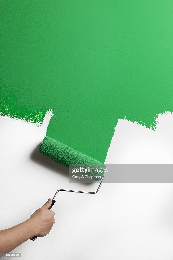 Green paint being rolled onto wall : Stock Photo