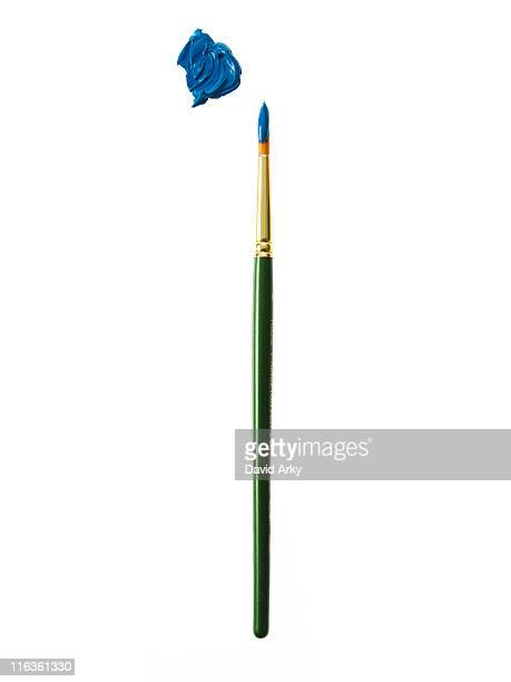 green paintbrush with blue paint on white background - paintbrush stock pictures, royalty-free photos & images