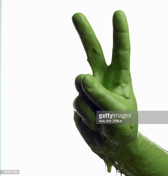 Green painted hand making peace sign