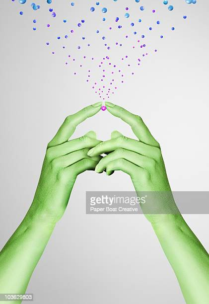 Green painted hands holding a pink metal ball