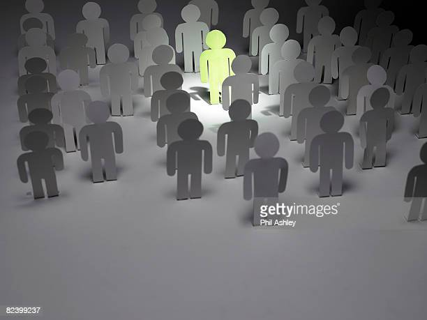 green paper man shines amongst a paper crowd