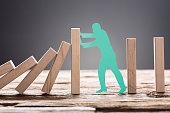 Green Paper Man Stopping Wooden Domino Blocks