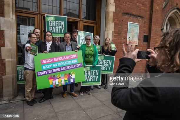 Green Party members and supporters hold placards as they pose for a photograph during a campaign event in which party coleader Jonathan Bartley and...