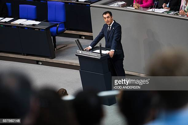 Green party MP Cem Oezdemir speaks next to the empty seats of Chancellor Angela Merkel and vice chancellor Sigmar Gabriel during a debate on...
