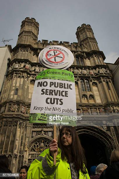 A Green Party protester demonstrates against the Tory coalition below Church Gate in Butter Market holding up a placard against public service cuts...