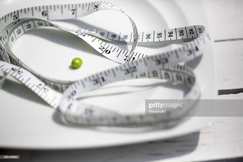 Green pea with measuring tape on plate, close up : Stock Photo