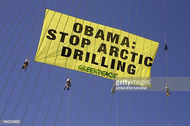 """Green Peace activists climb on the strings of Jerusalem's Chords Bridge during a protest on March 21 2013 to hang a banner saying """"Obama Stop Arctic..."""