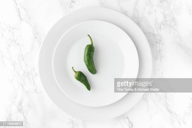 green pepper on white plate. bright background. minimalism. - green bell pepper stock pictures, royalty-free photos & images