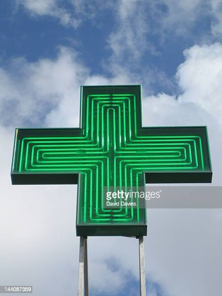 Green pharmacy sign against a cloudy sky