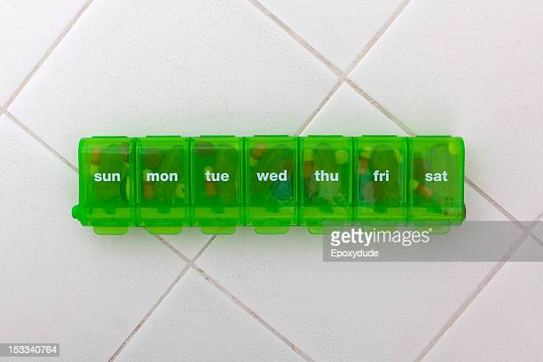 A green pill organizer with the abbreviated days of the week