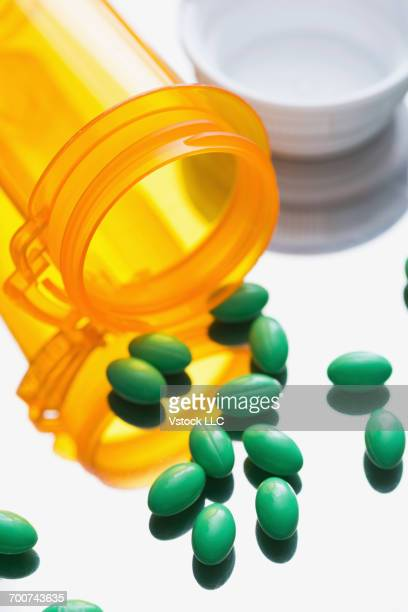 green pills and bottle - bottle green stock pictures, royalty-free photos & images