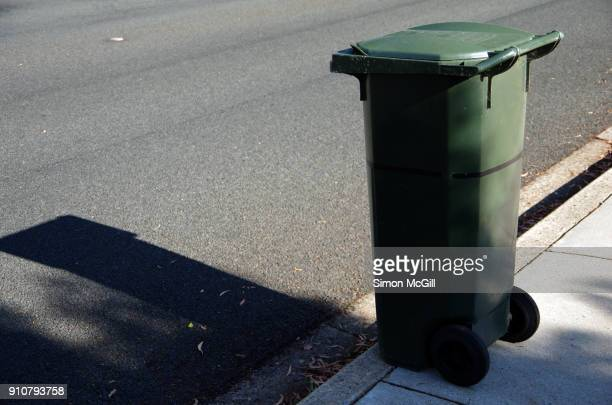 green plastic rubbish bin on the roadside kerb awaiting domestic waste collection - garbage bin stock pictures, royalty-free photos & images