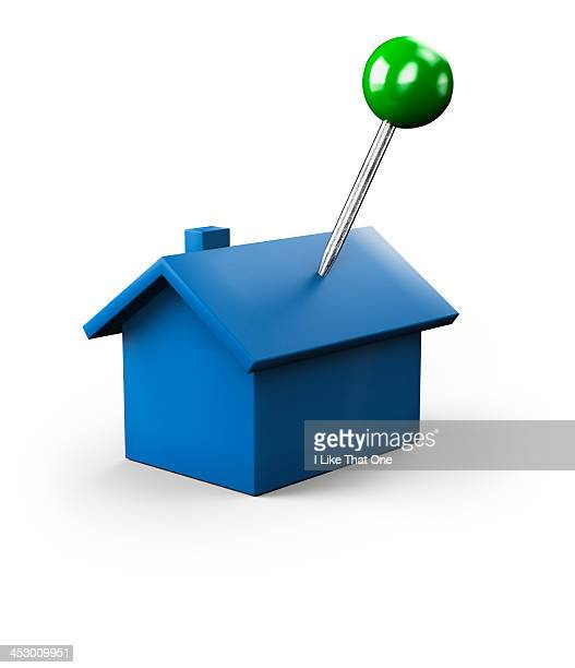 green push pin stuck into a blue house icon - home icon stock photos and pictures