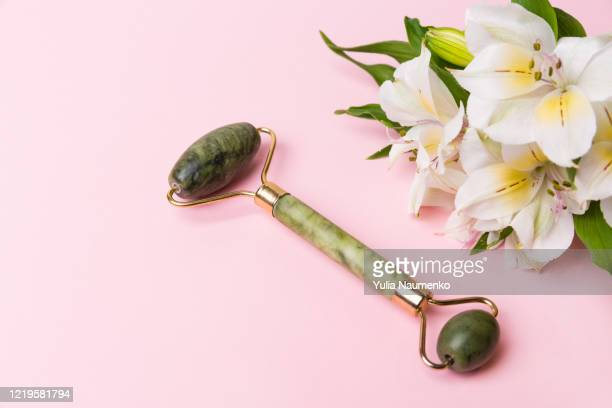 green quartz facial roller with alstroemeria on pink background. jade face massager, anti-aging, anti-wrinkle beauty skin care tool. - giada pietra foto e immagini stock