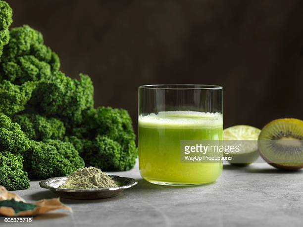 Green raw juice with halved kiwi and kale