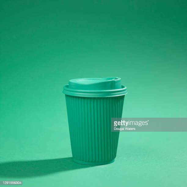 green recyclable cup against green background. - sustainable lifestyle stock pictures, royalty-free photos & images