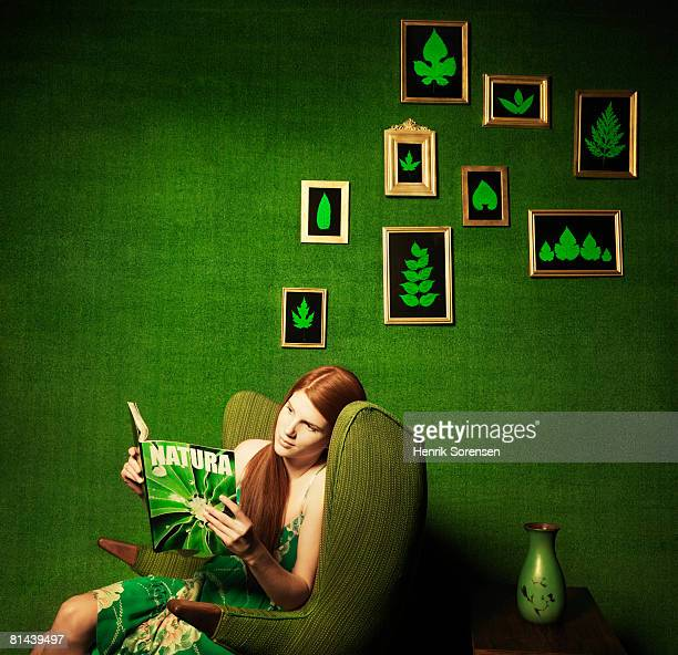 green room with pictures of leaves on the wall and woman reading a magazine. - nature magazine stock pictures, royalty-free photos & images