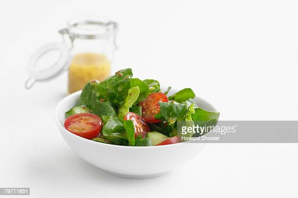 green salad in a white bowl, studio shot - green salad stock pictures, royalty-free photos & images