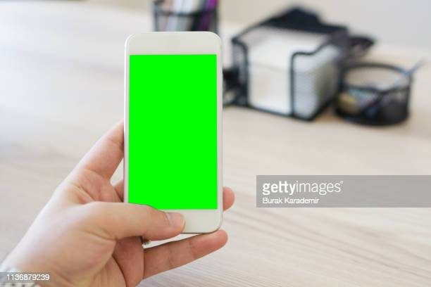 green screen handheld smartphone - chroma key foto e immagini stock