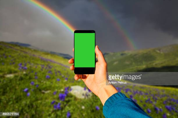 Green Screen Handheld Smartphone. Rainbow over flowers in the mountains