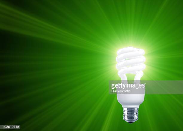 green shine of compact fluorescent light bulb - energy efficient lightbulb stock photos and pictures