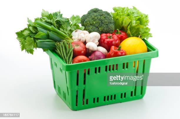 Green shopping basket filled with vegetables