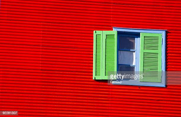 Green Shuttered Window in Red Wall Very Colorful