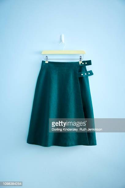 green skirt hanging on wall - green skirt stock pictures, royalty-free photos & images