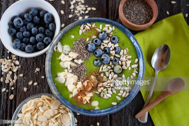 green smoothie bowl with almonds, blueberries, chia and sunflower seeds - bowl stock pictures, royalty-free photos & images