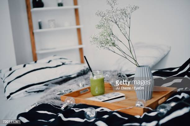 Green Smoothie By Flower Vase In Tray On Decorated Bed At Home