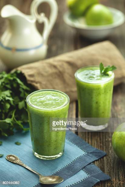 Green smoothie healthy drink in faceted glass on wooden table.