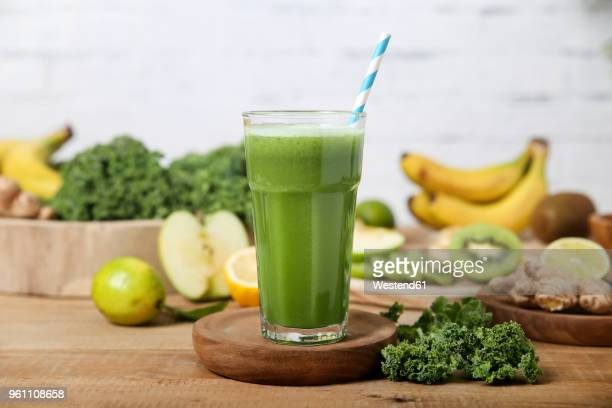Green smoothie surrounded by ingredients
