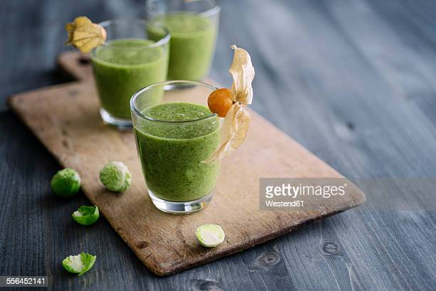 Green smoothie with brussel sprout, banana and apple juice garnished with physalis