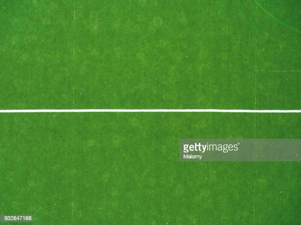 Green soccer or football field with white line on artificial grass.