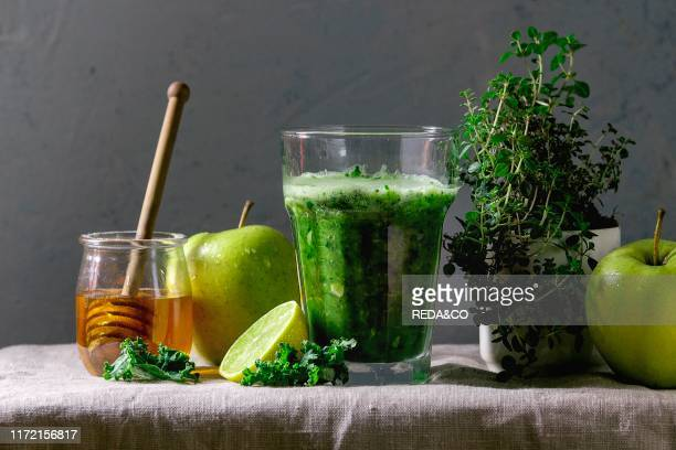 Green spinach kale apple honey smoothie in glass on linen table cloth with ingredients above Healthy organic eating