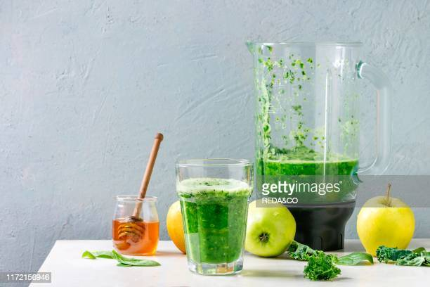 Green spinach kale apple honey smoothie in glass on white marble table with blender and ingredients above Healthy organic eating