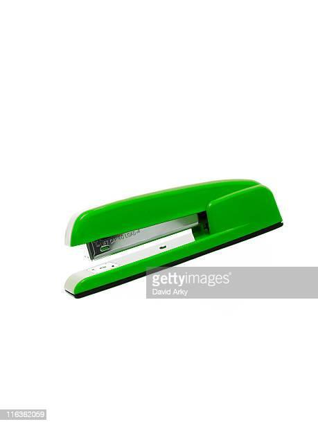 Green stapler on white background