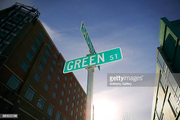 Green street sign with buildings