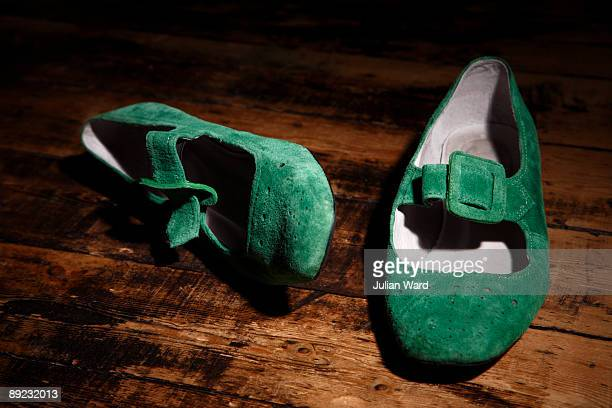 Green suede shoes on a wooden floor at night