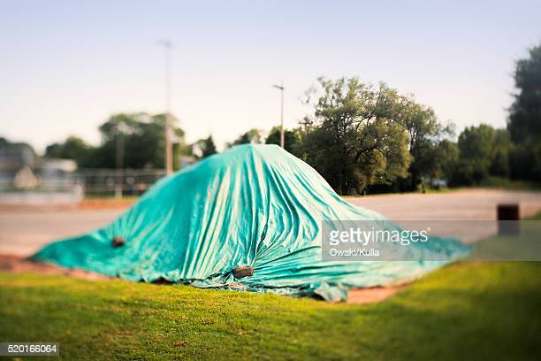 green tarp over pile in corner of parking lot - tarpaulin stock pictures, royalty-free photos & images