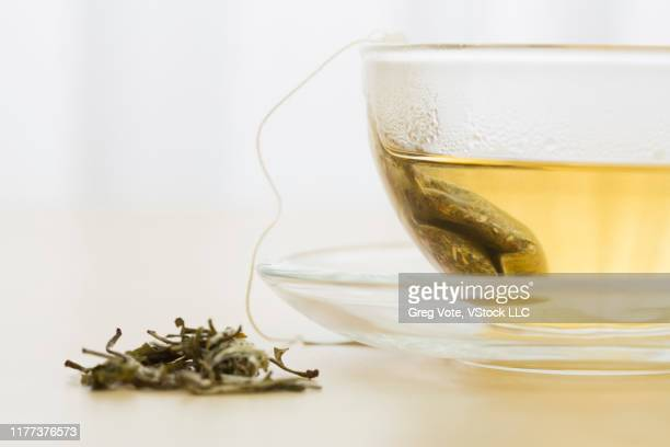green tea bag in cup and green tea leaves - steeping stock pictures, royalty-free photos & images