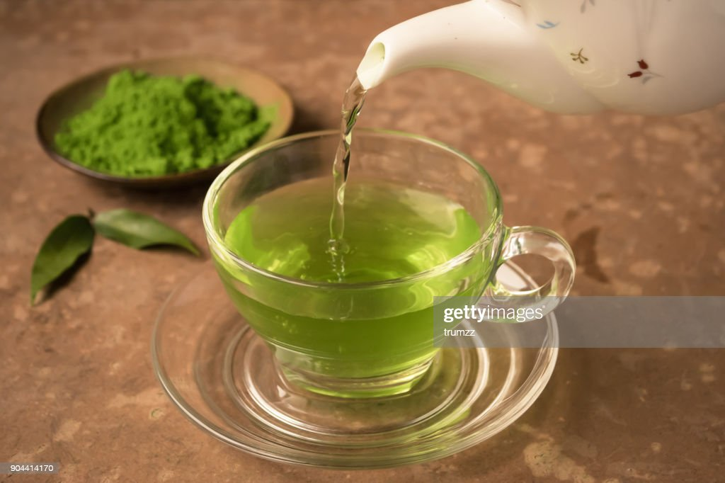 Green tea being poured into glass tea cup on the table : Stock Photo
