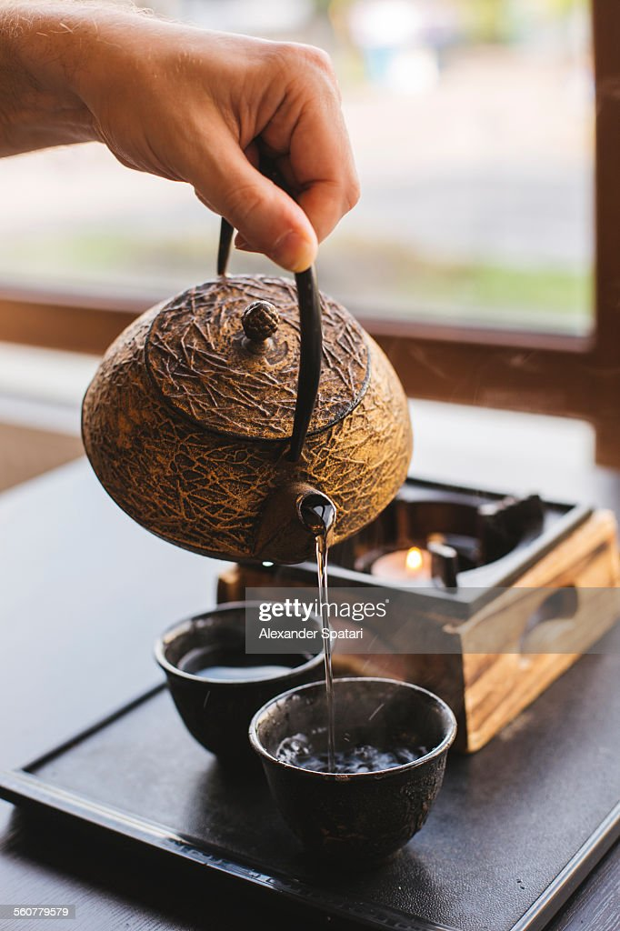 Green tea is being poured in a cup by a man : Stock Photo