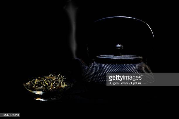 Green Tea Leaves In Bowl By Teapot Emitting Smoke Against Black Background