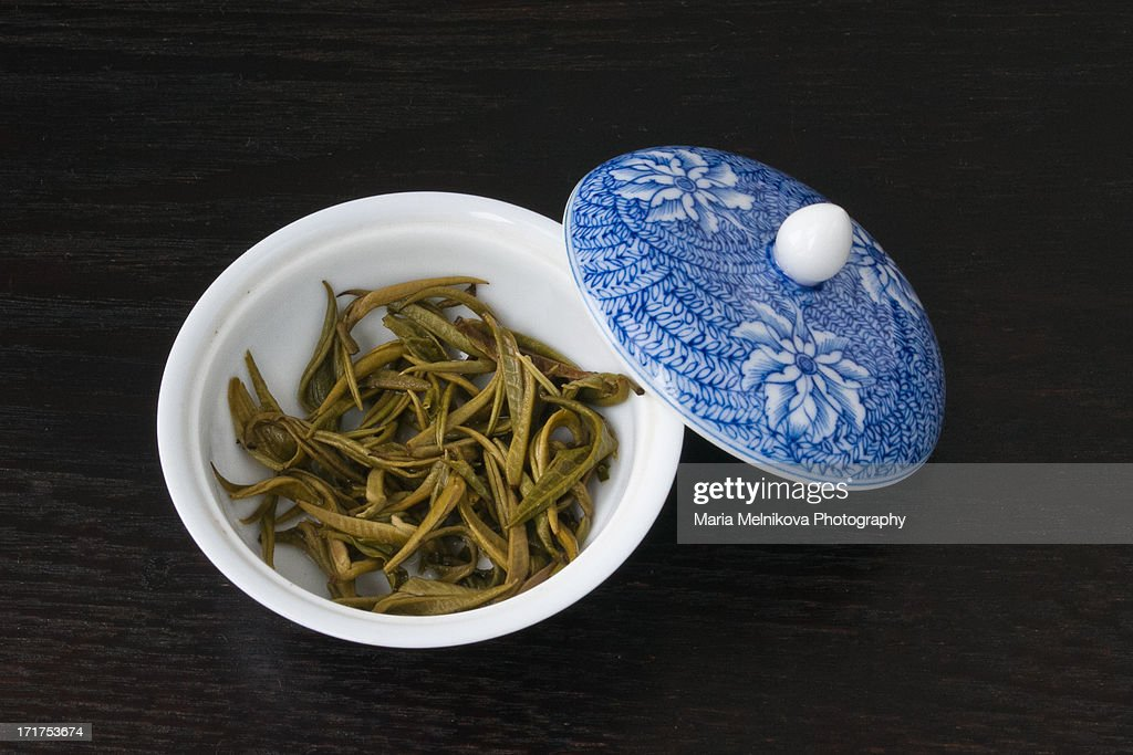 Green tea leaves in porcelain cup : Stock Photo