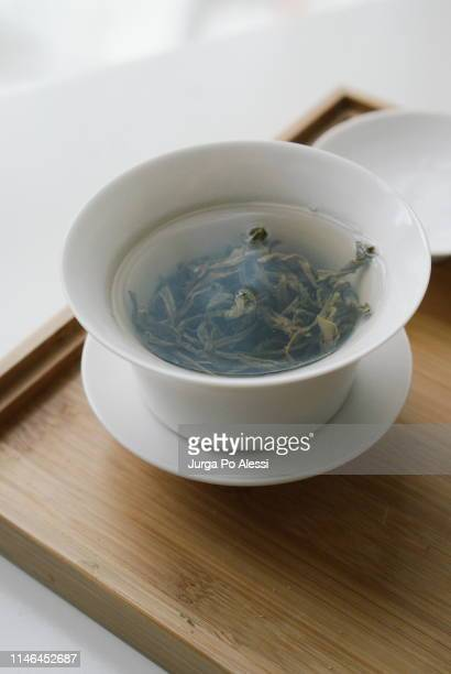 green tea leaves steeped in a white porcelain cup on wooden tea tray. - steeping stock pictures, royalty-free photos & images