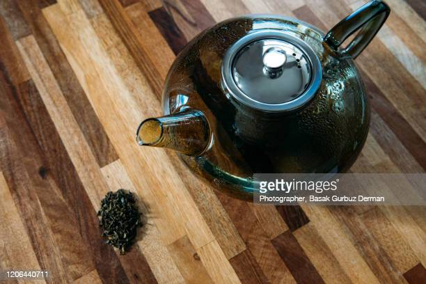 green tea leaves with teapot in background - english teapot stock pictures, royalty-free photos & images