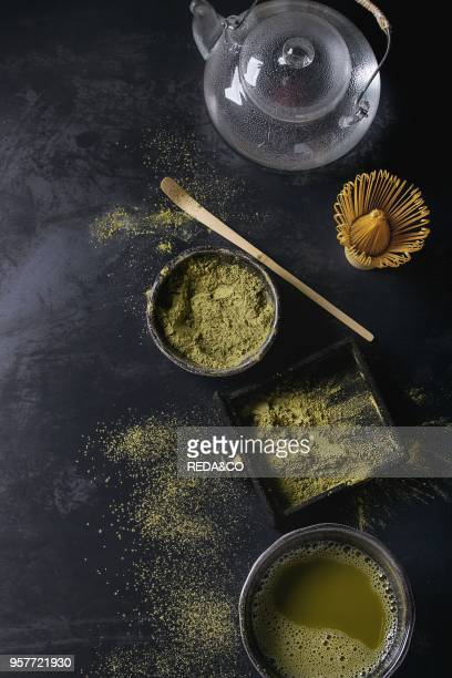 Green tea matcha powder and hot drink in black bowls and wood box standing with glass teapot bamboo traditional tools spoon whisk in terracotta tray...
