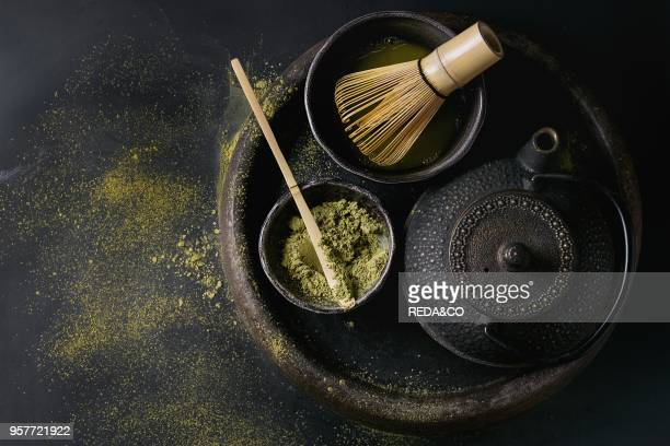Green tea matcha powder and hot drink in black bowls standing with iron teapot bamboo traditional tools spoon and whisk in terracotta tray over dark...
